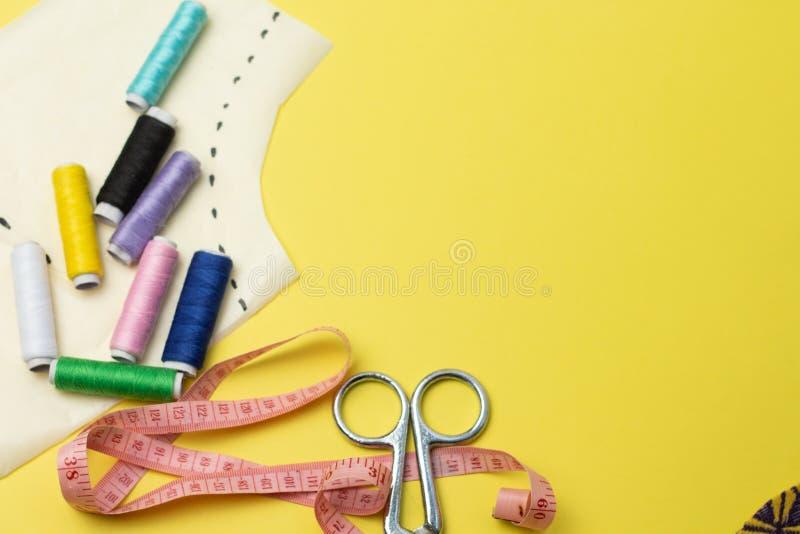 Sy tillbehör och tyg på en yelowbakgrund Sömnadtrådar, ben, modell och sycm För att sy hemma ?verkant fotografering för bildbyråer