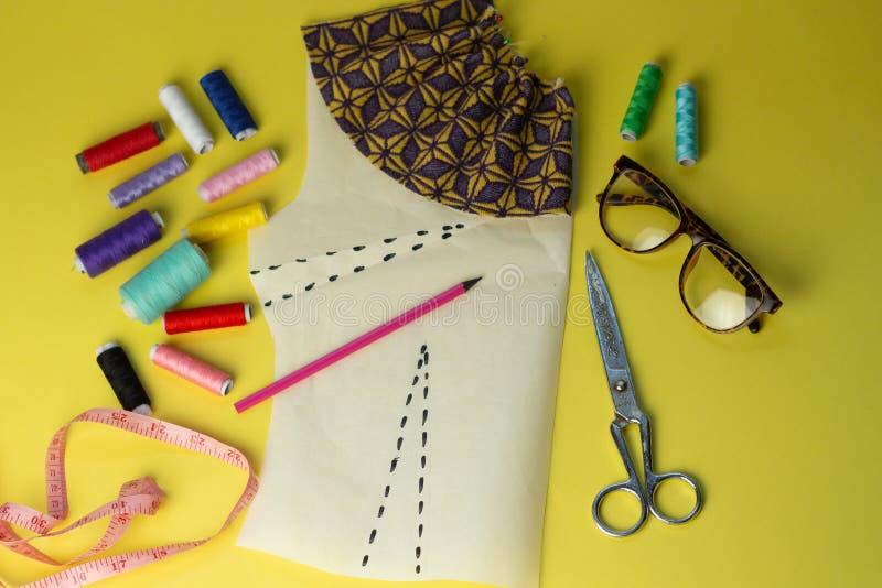 Sy tillbehör och tyg på en yelowbakgrund Sömnadtrådar, ben, modell och sycm För att sy hemma ?verkant royaltyfri fotografi