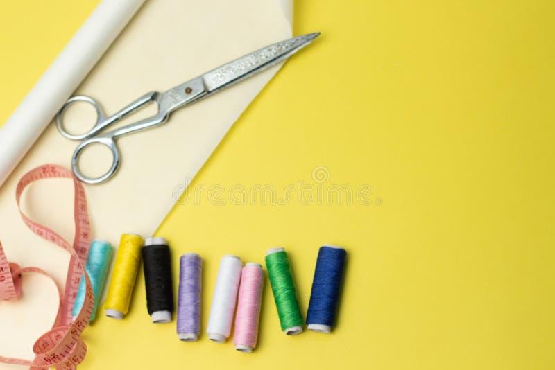 Sy tillbehör och tyg på en yelowbakgrund Sömnadtrådar, ben, modell och sycm För att sy hemma ?verkant royaltyfria bilder
