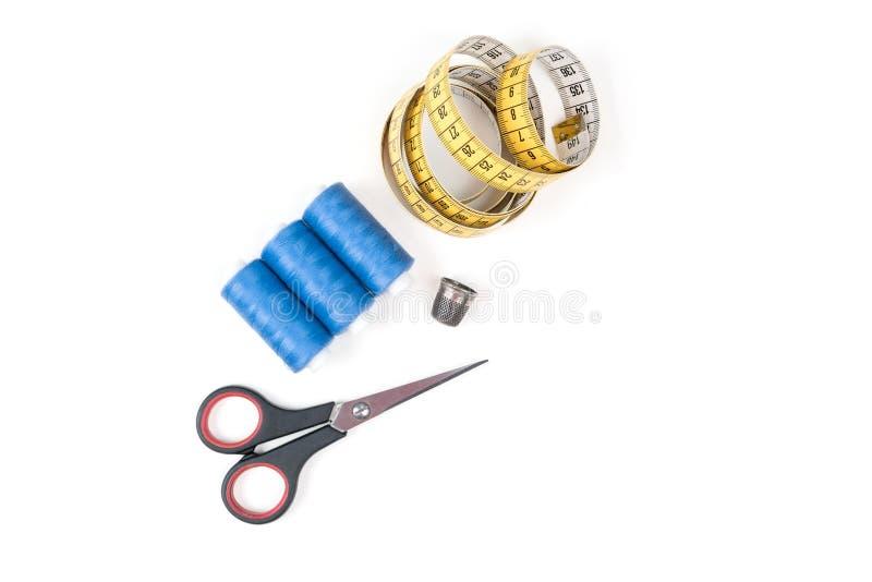Sy tillförsel och hjälpmedel, tre blåa sömnadtrådar, gult mäta band med svartnummer, liten stängd sax och metallth royaltyfri bild