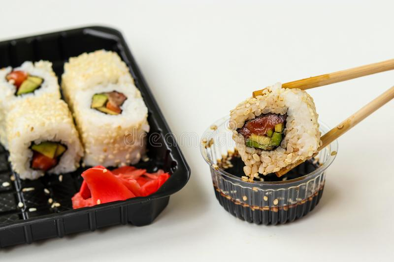 Syake rolls in a set of 6 pieces in a black box, with ginger, wasabi and soy sauce, fast food, horizontal orientation. Closeup stock photos