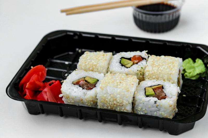 Syake rolls in a set of 6 pieces in a black box, with ginger, wasabi and soy sauce, fast food, horizontal orientation. Closeup royalty free stock images