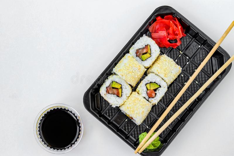 Syake rolls in a set of 6 pieces in a black box, with ginger, wasabi and soy sauce, fast food, horizontal orientation, top view. Syake rolls in a set of 6 pieces royalty free stock photos