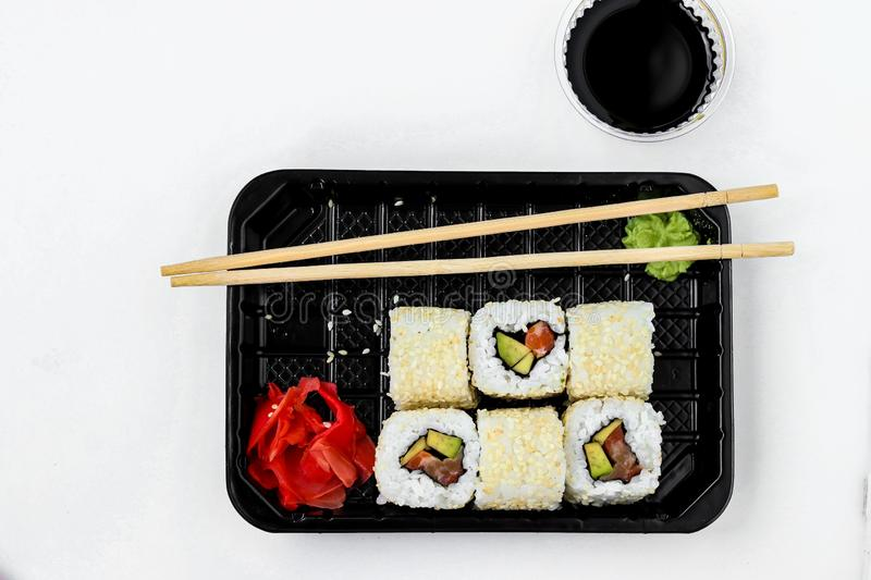 Syake rolls in a set of 6 pieces in a black box, with ginger, wasabi and soy sauce, horizontal orientation, top view. Syake rolls in a set of 6 pieces in a black stock image