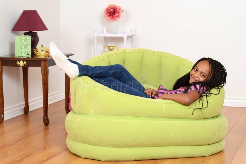 Sydafrikanskt barn som kopplar av i grön stol arkivfoto