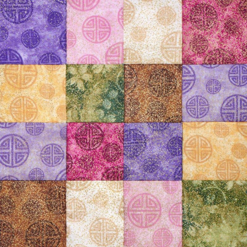 Sydde ljusa fyrkantiga stycken av tyger, del av täcket, traditionell patchwork royaltyfria bilder