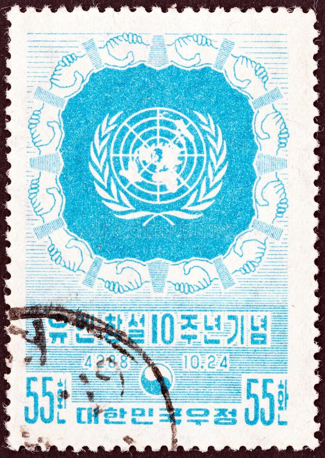 SYDKOREA - CIRCA 1955: En stämpel som skrivevs ut i Sydkorea, utfärdade för den 10th årsdagen av Förenta Nationerna visar embleme royaltyfri fotografi
