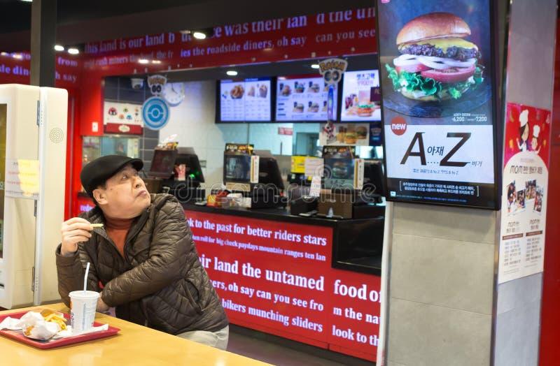 Sydkoreanskt mansammanträde på en snabbmatrestaurang royaltyfri fotografi