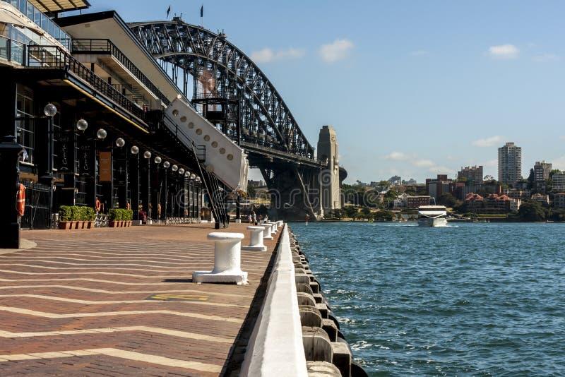 Sydney, Austrália - 12 de janeiro de 2009: Opinião Sydney Promenade com povos de passeio A ponte do porto é vista através da água foto de stock royalty free