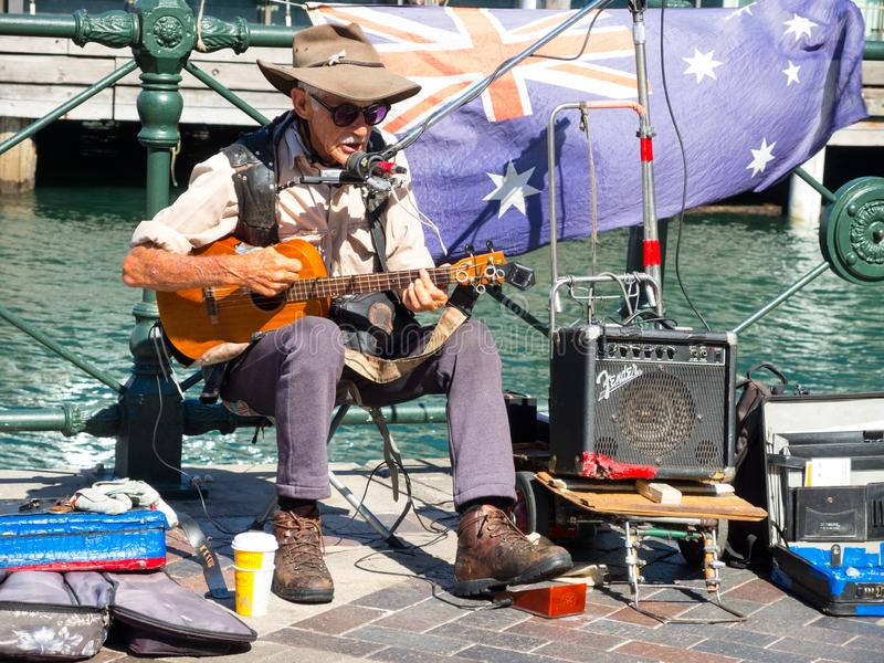 Old man Australian street guitarist performing at Circular Quay. royalty free stock image
