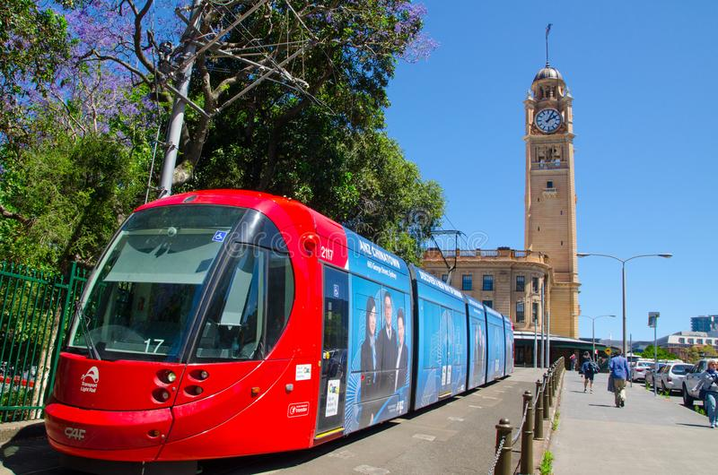 Red light rail running on the track at Pitt St. with Iconic central railway station clock tower at the background. royalty free stock photos