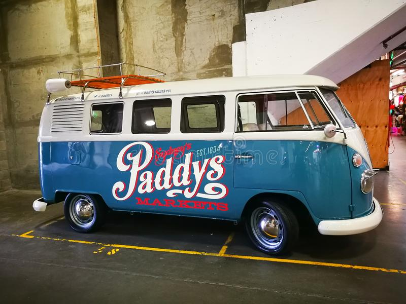 Vintage blue Volkswagen van displaying with Paddy`s market logo painted on it. stock images