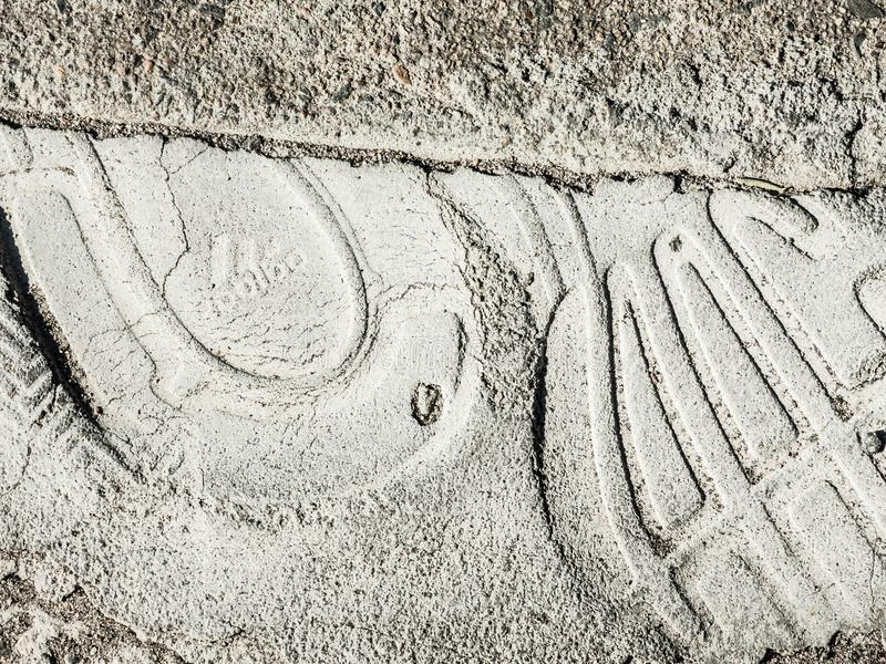 Foot prints from the shoe which is stamped ADIDAS shoe brand logo on the surface of a footpath in Sydney. stock photos