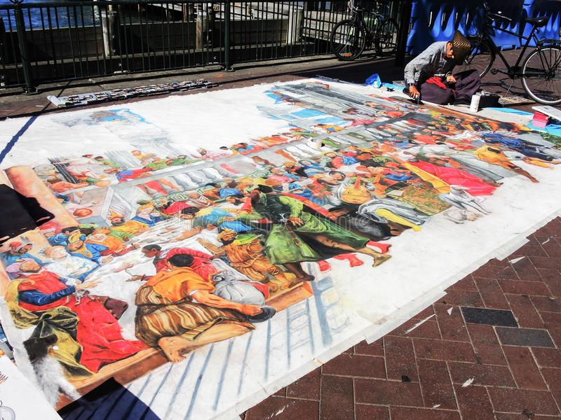 A street artist drawing on large piece of paper laid out on the floor at Sydney, Circular Quay. stock photo