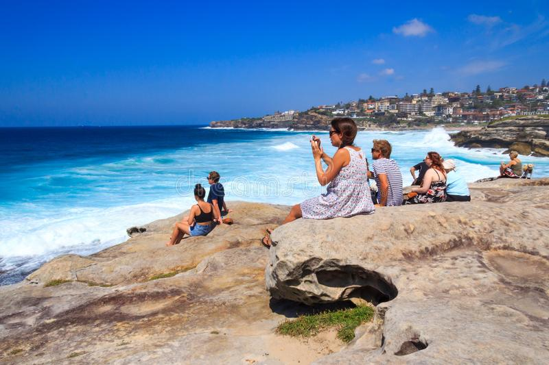 People sat on top of a cliff watching surfers at Bronte stock image