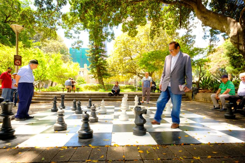 Happy time. The Old men are playing the giant chess together on royalty free stock image