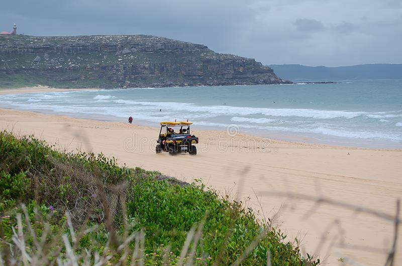Little surf rescue beach buggy car driving on Sydney palm beach. stock photography