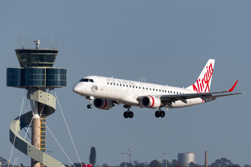 Virgin Australia Airlines Embraer E-190 twin engine regional jet airliner landing at Sydney Airport with the air traffic control t. Sydney, Australia - October 7 royalty free stock photos