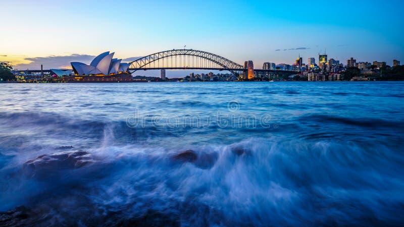 Sydney Australien - november 8, 2018: horisont med operan och bron för sydney hamn på solnedgången royaltyfria foton
