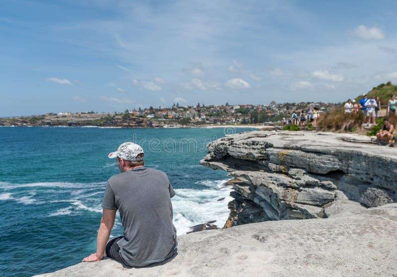 SYDNEY AUSTRALIEN - NOVEMBER 07, 2014: Oidentifierade Person Sitting på kanten av vaggar, nästan havet i Sydney, Australien royaltyfri foto