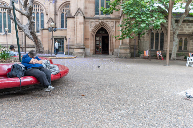SYDNEY, AUSTRLIA - NOVEMBER 10, 2014: People Sleeping on the Bench in Sydney, in fron of St Andrew's Cathedral. People Sleeping on the Bench in Sydney, in fron stock photography