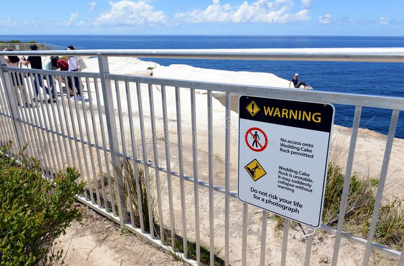 Tourists engaging in risky behavior in Royal National Park, Sydney Australia. SYDNEY CIRCA NOVEMBER 2017. Despite warning signs to stay off the cliff and recent royalty free stock photo