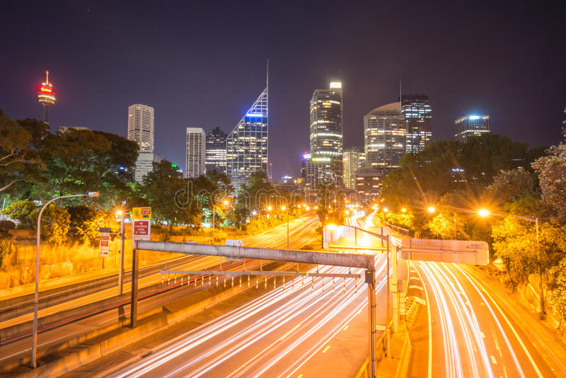 Sydney City Skyline at Night. Beautiful scene of colorful Sydney city skyline at night with light trail from the moving car at street stock image