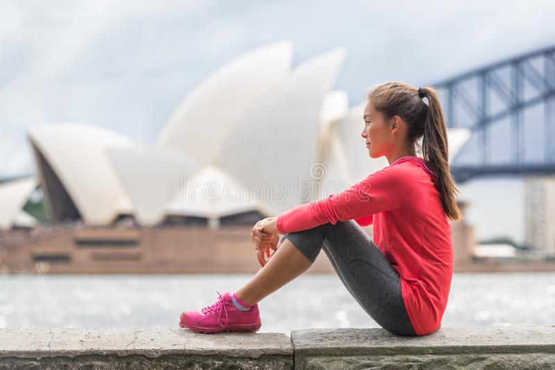 Sydney city woman living an active lifestyle relaxing at urban park after running cardio exercise outside in summer. Asian girl. Sitting with Sydney tourist stock photography