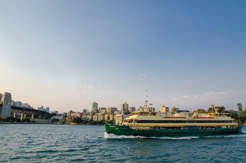 Sydney hamn med färjan i solnedgångljus och cityscapesikt bakom royaltyfria bilder
