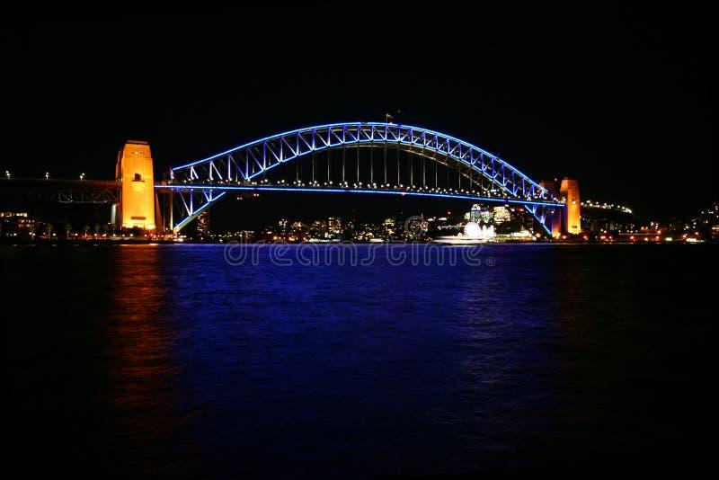 Sydney Harbor Bridge en luz azul en la noche Reflexión del agua que brilla intensamente Nightscape icónico de la costa de la ciud imagenes de archivo