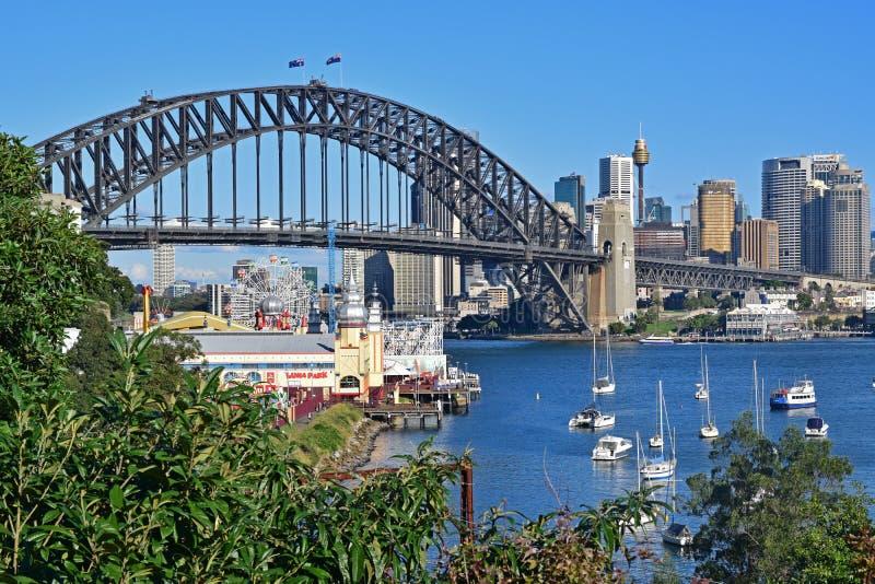 Sydney Harbour Bridge e Luna Park Sydney con le foglie da Wendy Secret Garden visibile in priorità alta immagini stock