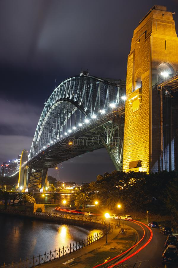 Sydney Harbour Bridge en la noche, iluminada por las luces con la cola larga de la exposición se enciende de un coche, fotografía de archivo