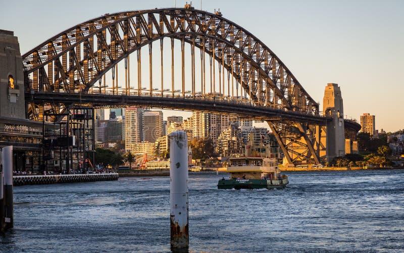 Sydney Harbour Bridge im goldenen Sonnenunterganglicht mit Fähre in Vordergrund eingelassenem Sydney, Australien stockbild