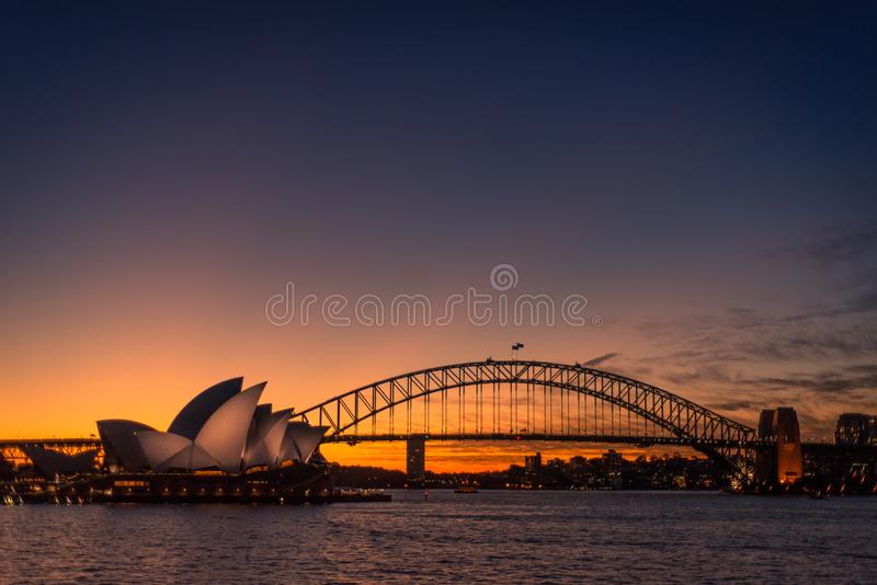 Sydney, New South Wales / Australia - May 17th 2016: Sydney Opera House lit up with light at night time with Harbour Bridge to the royalty free stock photography