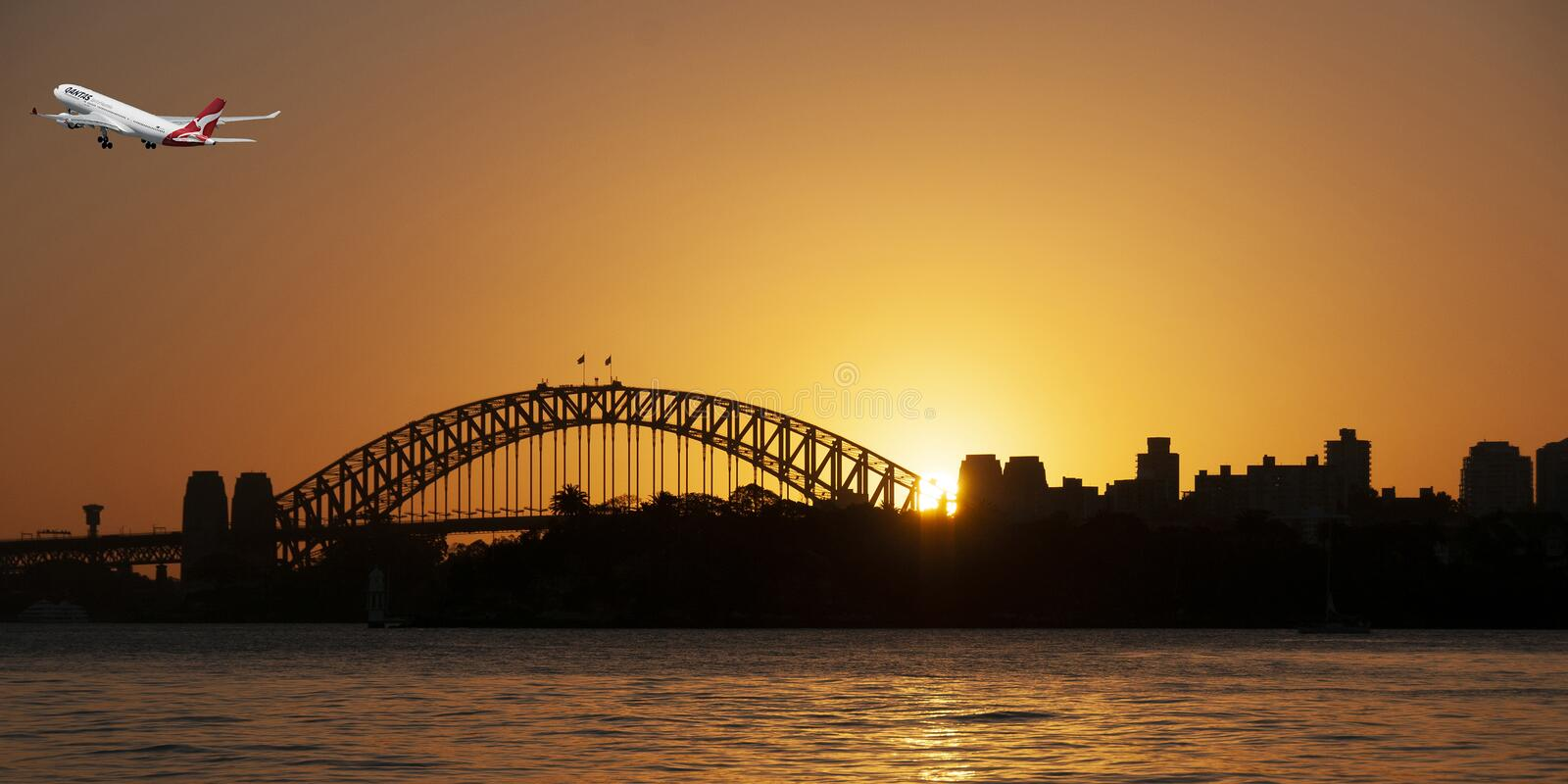 Aircraft in flight departing Sydney in an orange sunset sky. stock image
