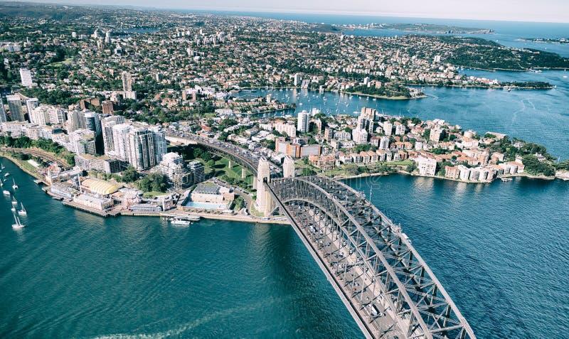 SYDNEY - NOVEMBER 10, 2015: Panorama- flyg- sikt av Sydney Harbor Bridge på en solig dag Sydney tilldrar 20 miljoner varje folk arkivbilder
