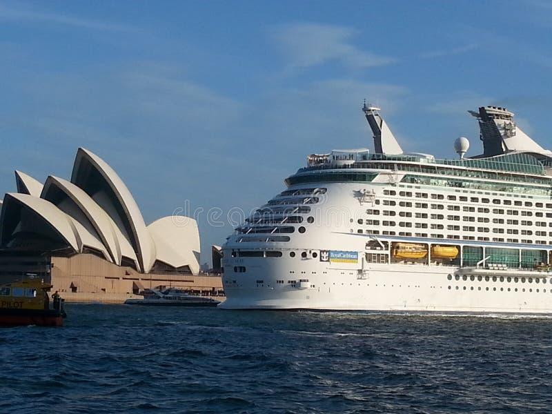Sydney Opera House con el barco de cruceros enorme que pasa pasado hacia fuera al mar abierto fotos de archivo