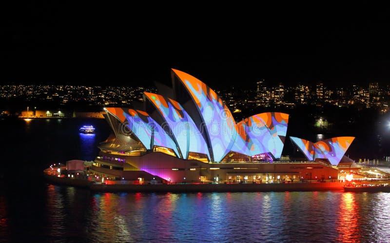 Sydney Opera House i apelsin och blått under livliga Sydney arkivbilder
