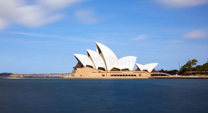 Sydney Opera House met onscherpe water en wolken royalty-vrije stock foto