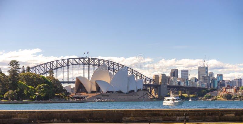 Sydney Opera House och Harbour bridge med båt och byggnader i bakgrunden på den soliga klara himmeldagen, Sydney Opera House och arkivfoto