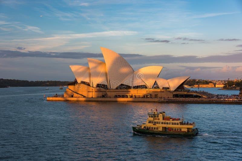 Sydney Opera House på solnedgången med färjan på förgrund royaltyfri foto