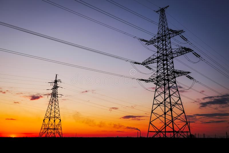 Sylhouette: wieże elektryczne wysokiego napięcia w zachodzie słońca Linie elektroenergetyczne wysokiego napięcia Elektryczna stac obrazy royalty free