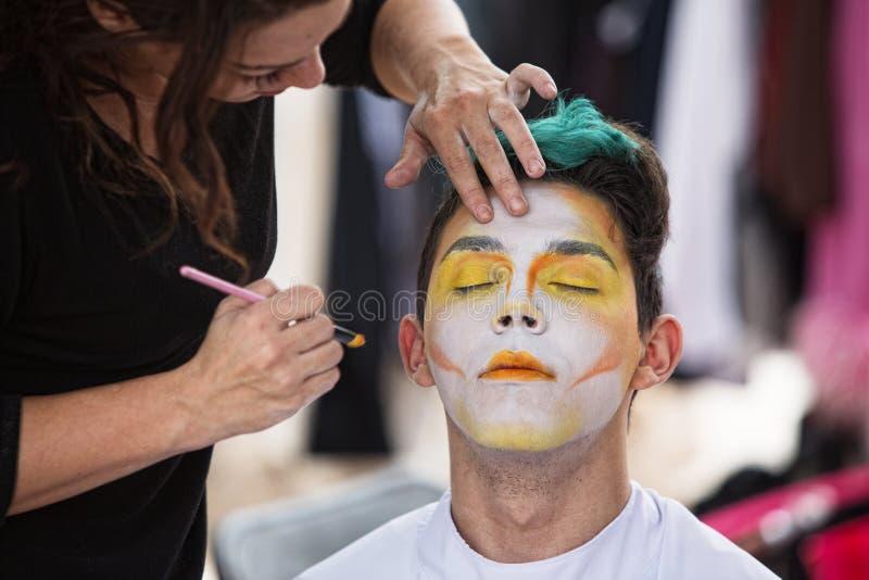Sylist que pone maquillaje en payaso fotos de archivo