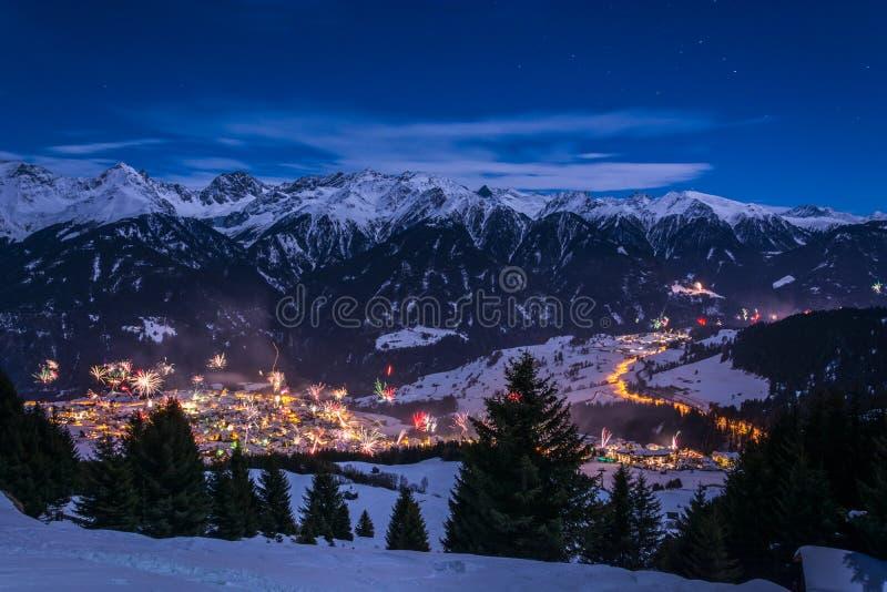 Sylvesterabende Feuerwerke über Dorf Fiss in Österreich mit schneebedecktem lizenzfreie stockfotografie