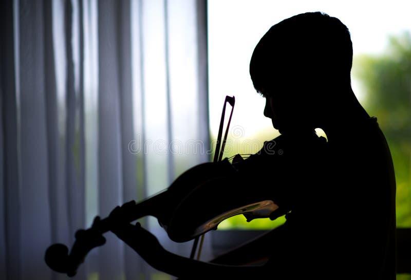 sylwetek chłopiec bawić się skrzypce w muzycznym klasowym pokoju i ćwiczą obrazy royalty free