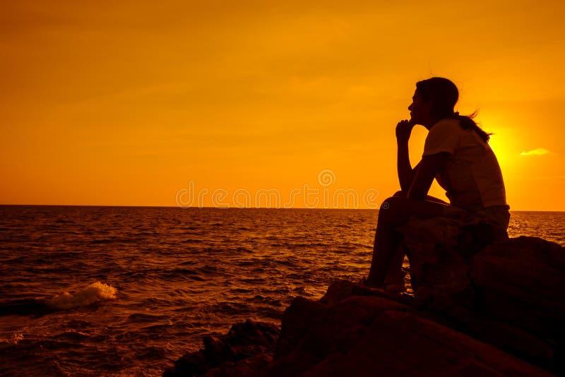 Sylwetek kobiety siedzi samotnie na skale zdrowie mentalne zdjęcie stock