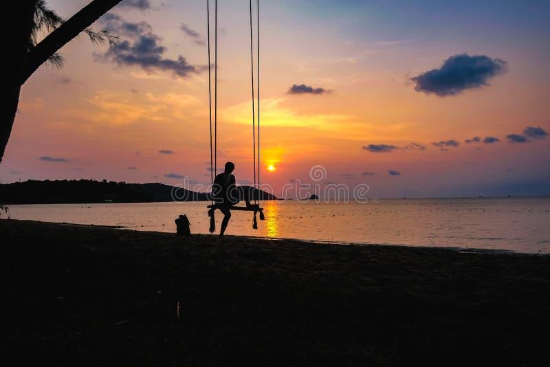 Sylwetek ludzie siedzą na huśtawce z piękną zmierzch chmurą s fotografia royalty free