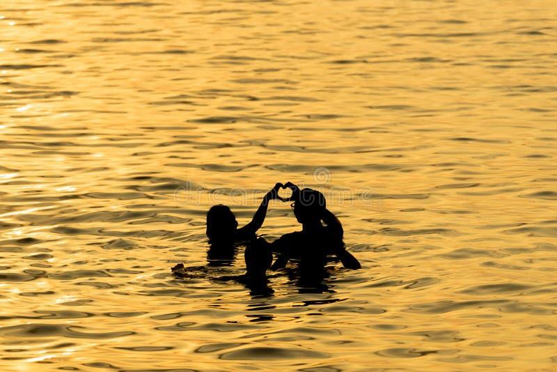 Sylwetek ludzie w złotym morzu z parą kochają działanie obrazy stock