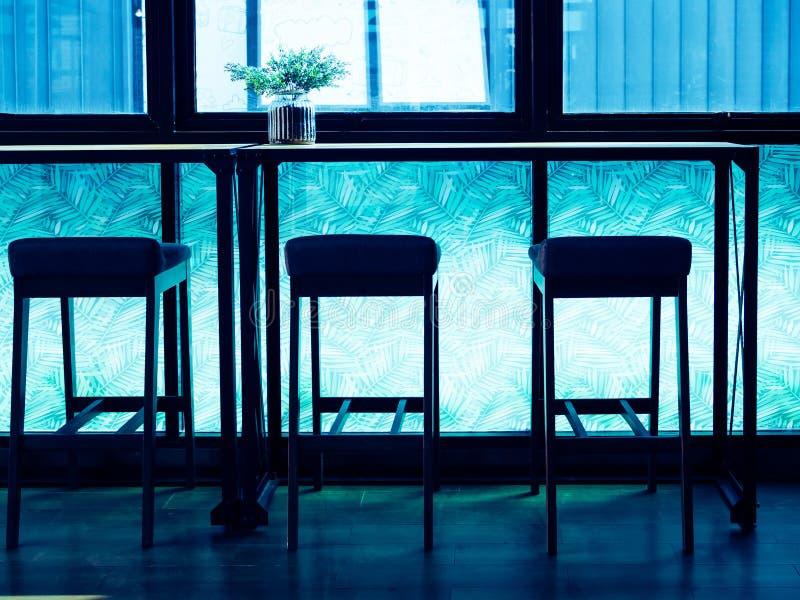 Sylwetek prętowe stolec i drewniany kontuaru bar blisko nadokiennego szkła na błękicie zaświecają pokój zdjęcia royalty free