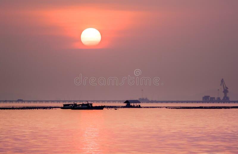 Sylwetka łódź i most handlowy dok przy morzem z zmierzchu niebem obrazy stock